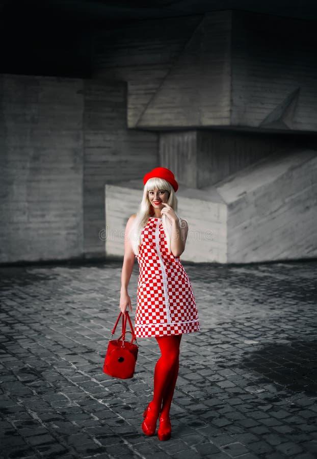 Una ragazza bionda in un vestito dal percalle immagini stock