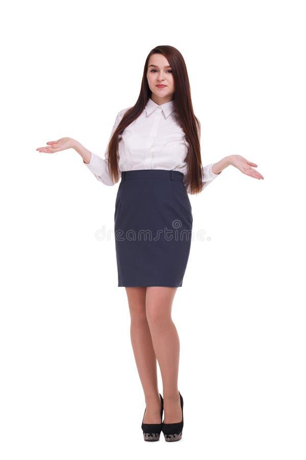Una ragazza, in una blusa, gonna e tacchi alti, sta tenente le sue mani ai lati isolamento fotografie stock