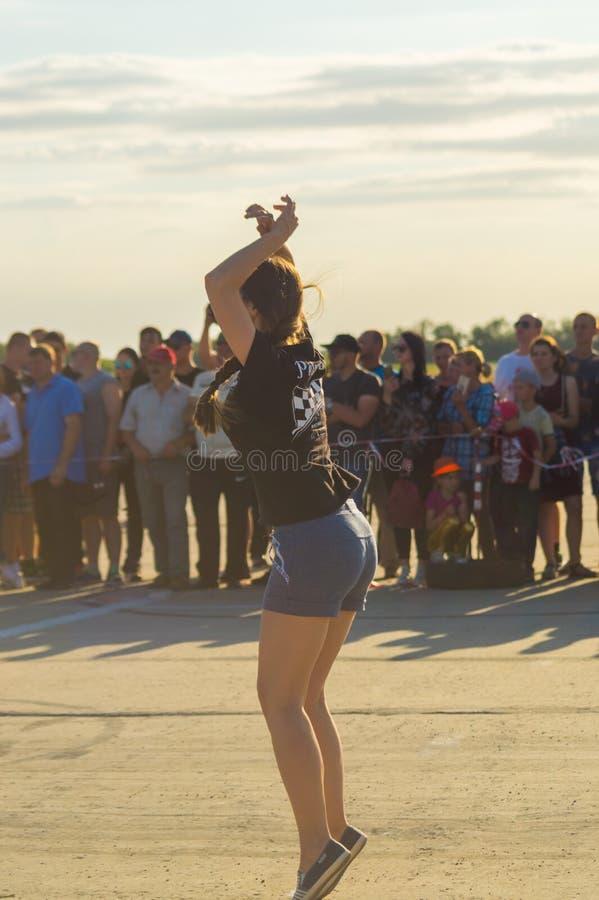 Una ragazza in breve e cavalieri d'ondeggiamento di una maglietta al segnale della corsa immagini stock