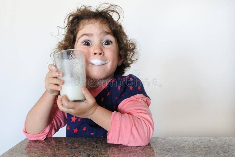 Una ragazza a buon mercato beve latte fotografia stock