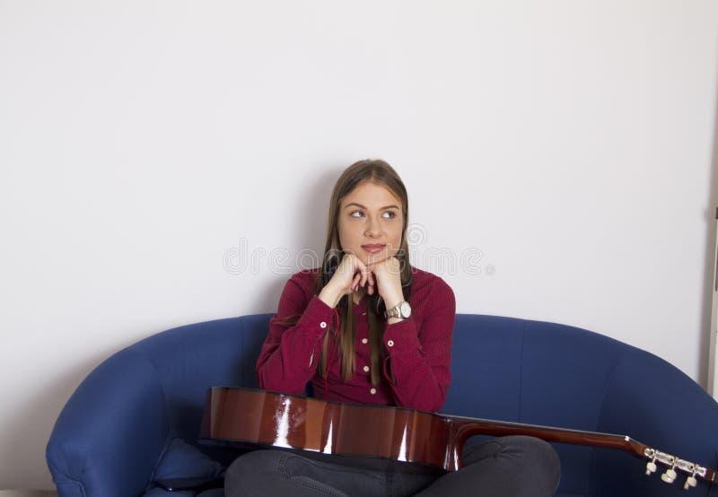 Una ragazza in una camicia rossa che si siede su una doppia sedia fotografia stock