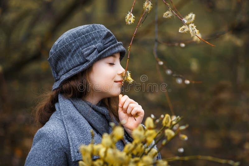Una ragazza in cappotto grigio ed in un cappello grigio sveglio nella foresta in molla in anticipo con un ramo del salice dei ram fotografie stock