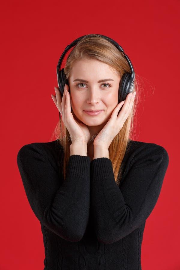 Una ragazza castana, ascoltante la musica in cuffie e sorridente, pungente le cuffie con le mani fotografie stock