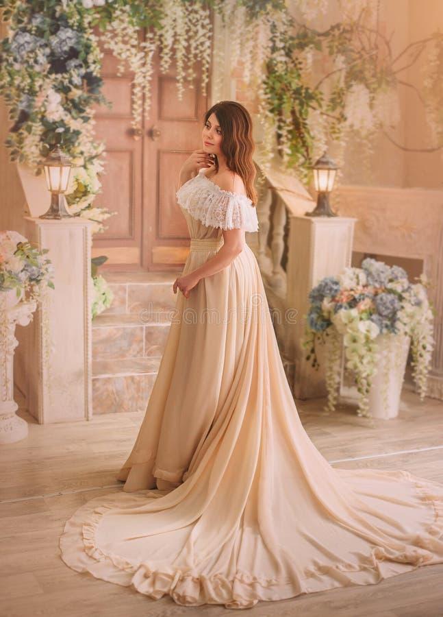 Una ragazza castana in un vestito d'annata crema con le spalle aperte e con un bello treno lungo Posa di modello contro la a fotografie stock