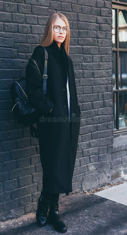 Una ragazza casuale dei pantaloni a vita bassa con capelli biondi lunghi che indossano un cappotto alla moda ed i vetri rotondi m immagini stock