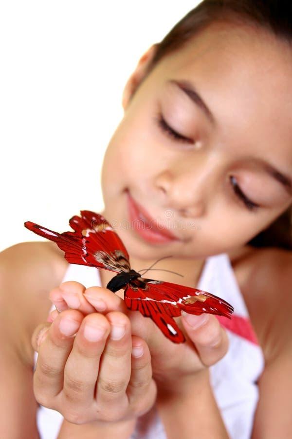 Una ragazza che ammira una bella farfalla rossa immagine stock libera da diritti