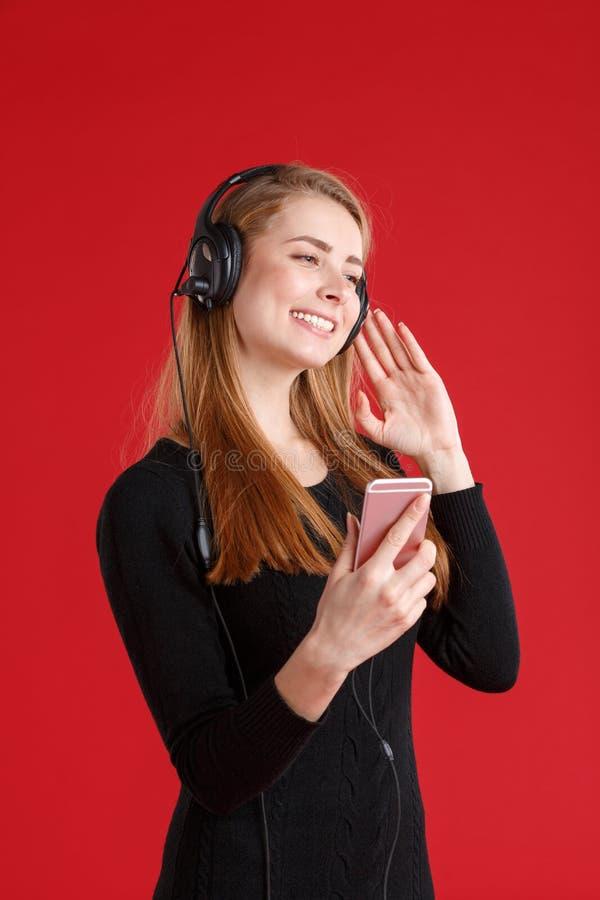Una ragazza che ascolta la musica in cuffie con il telefono cellulare e che sorride felicemente Su un fondo rosso immagine stock libera da diritti