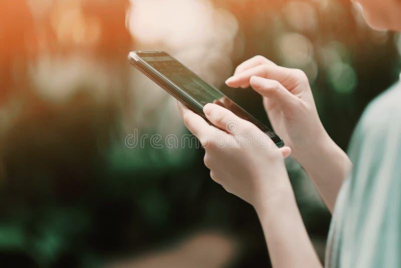 Una ragazza che cerca alcuni dati dal suo smartphone immagine stock