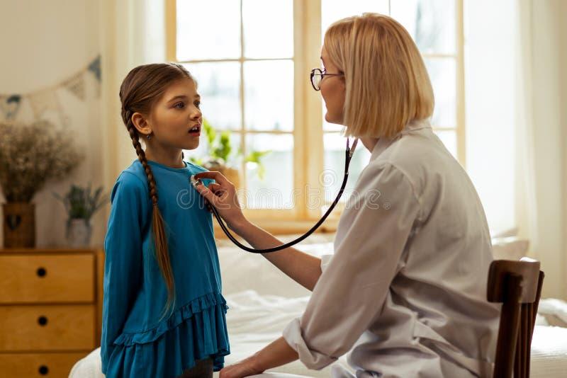 Una ragazza che espira mentre un medico che esamina i suoi polmoni fotografia stock