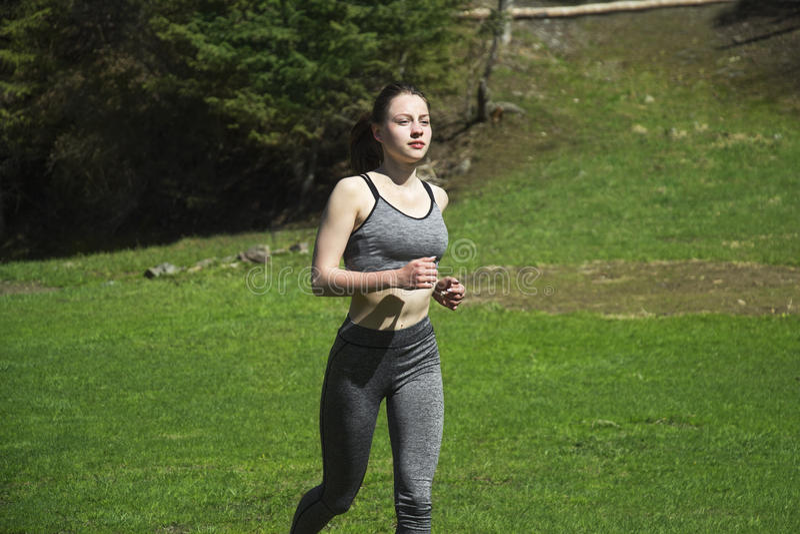 Una ragazza che fa gli sport nelle montagne fotografia stock