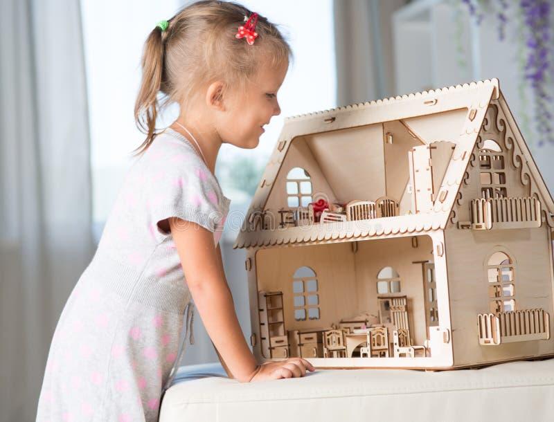 Una ragazza che gioca con una casa delle bambole fotografie stock libere da diritti