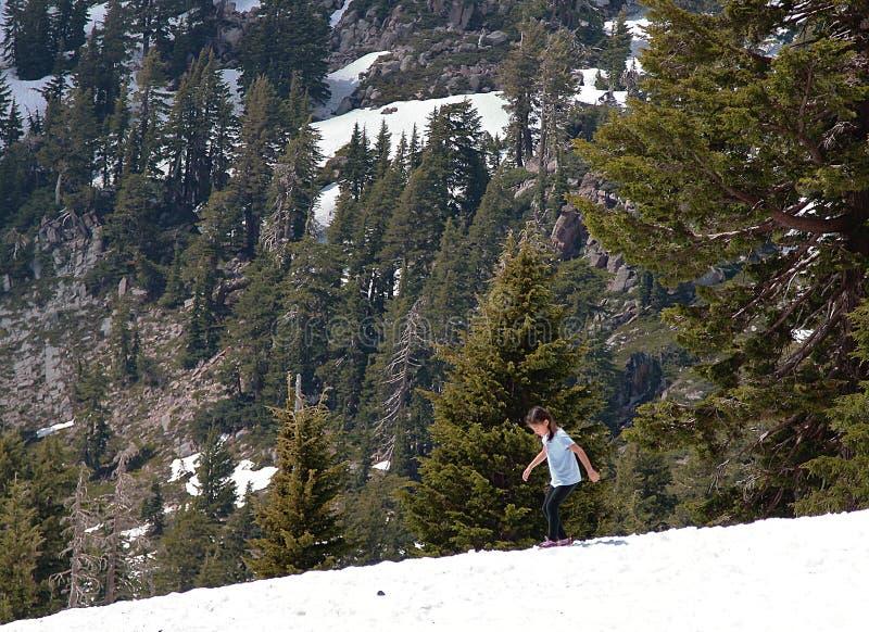 Una ragazza che gioca con la neve verso la metà dell'estate nelle montagne fotografia stock