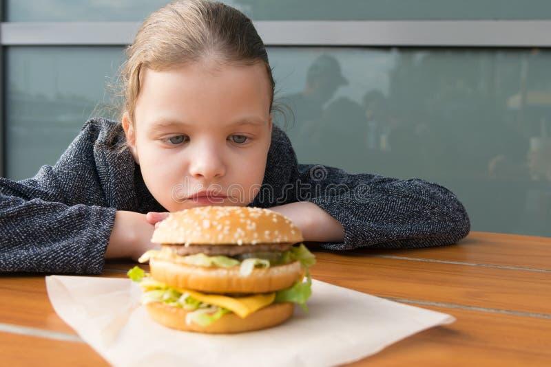 Una ragazza che guarda Burger appetitoso che sta davanti a lei sul tavolo fotografie stock libere da diritti