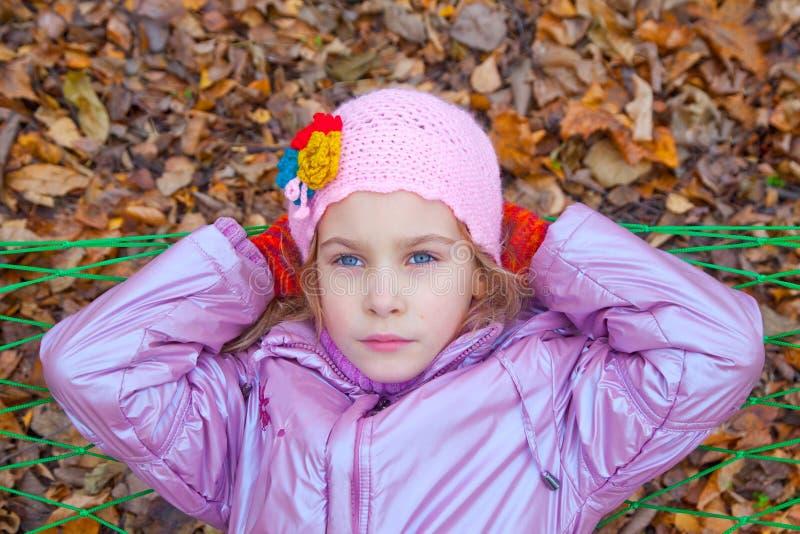 Una ragazza che guarda su e che oscilla in un'amaca fotografie stock