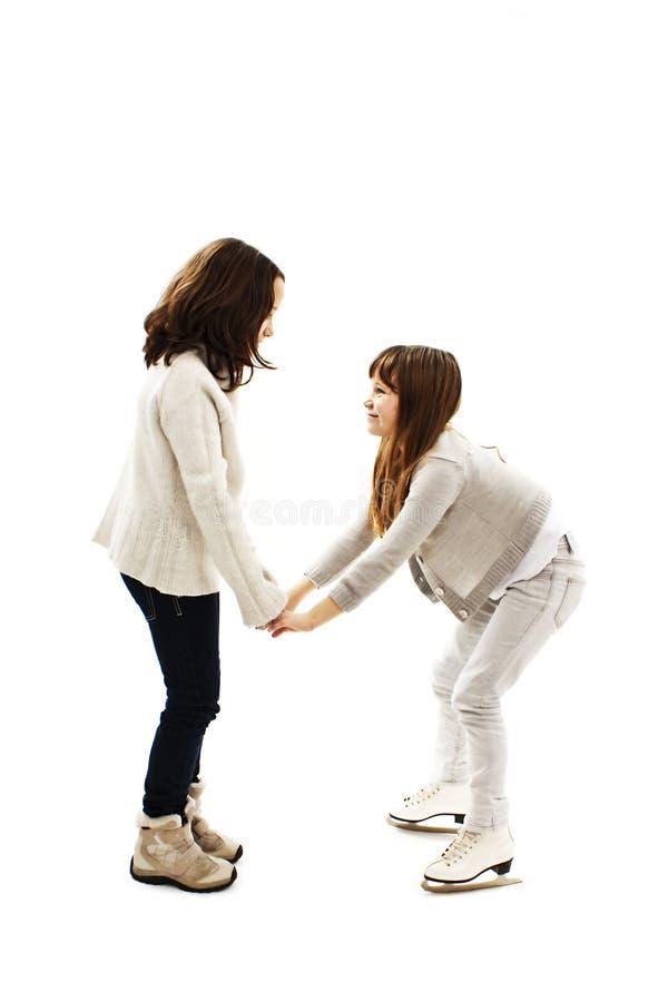 Una ragazza che insegna a sua sorella a pattinare su ghiaccio immagine stock libera da diritti