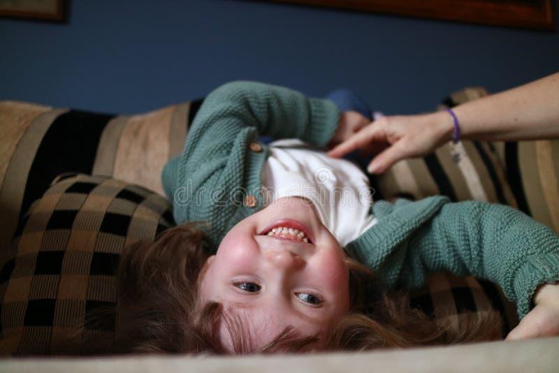 Una ragazza che ottiene solleticata da un membro della famiglia sul sofà fotografia stock