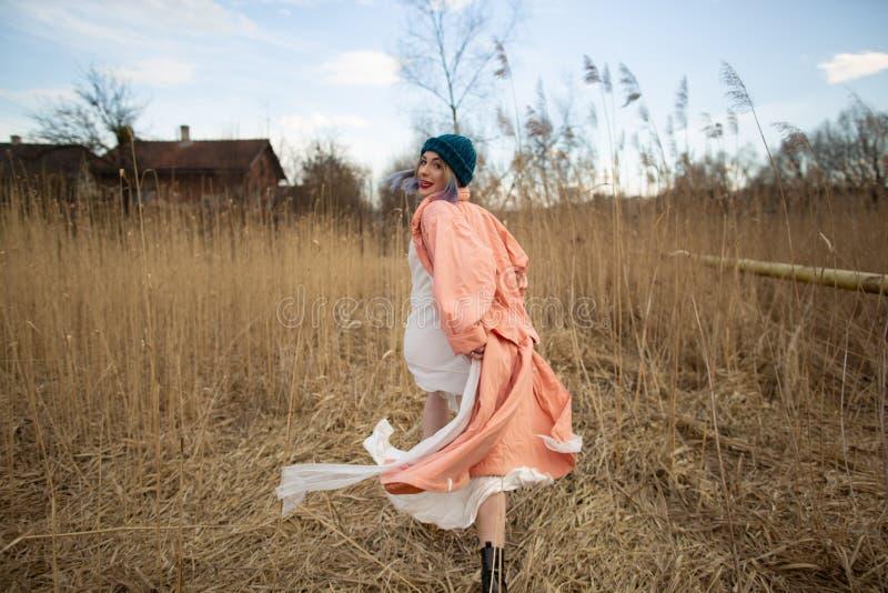 Una ragazza che porta un cappotto pastello e un cappello alla moda posa in un giacimento di grano Viev posteriore fotografia stock libera da diritti