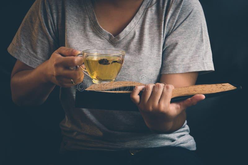 Una ragazza che si rilassa il tè caldo colto della bevanda e del libro immagine stock