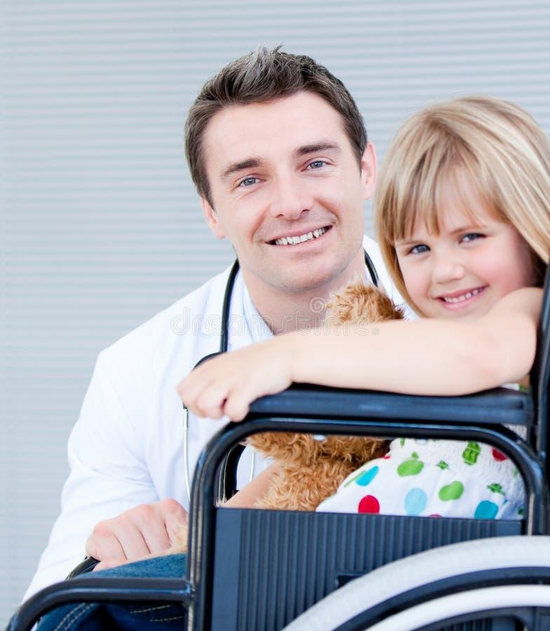 Una ragazza che si siede su una sedia a rotelle con il suo medico immagini stock