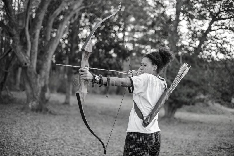 Una ragazza che tende arco e freccia nella foresta fotografia stock libera da diritti