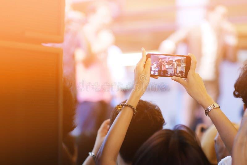 Una ragazza che utilizza il suo smartphone per la presa un'immagine nel concerto di musica immagine stock