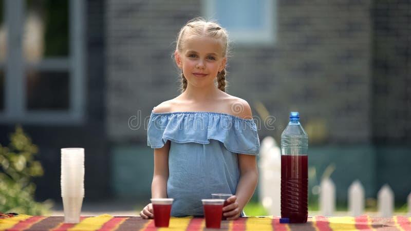 Una ragazza che vende limonata in un cantiere, prima guadagna, bevande biologiche fotografia stock