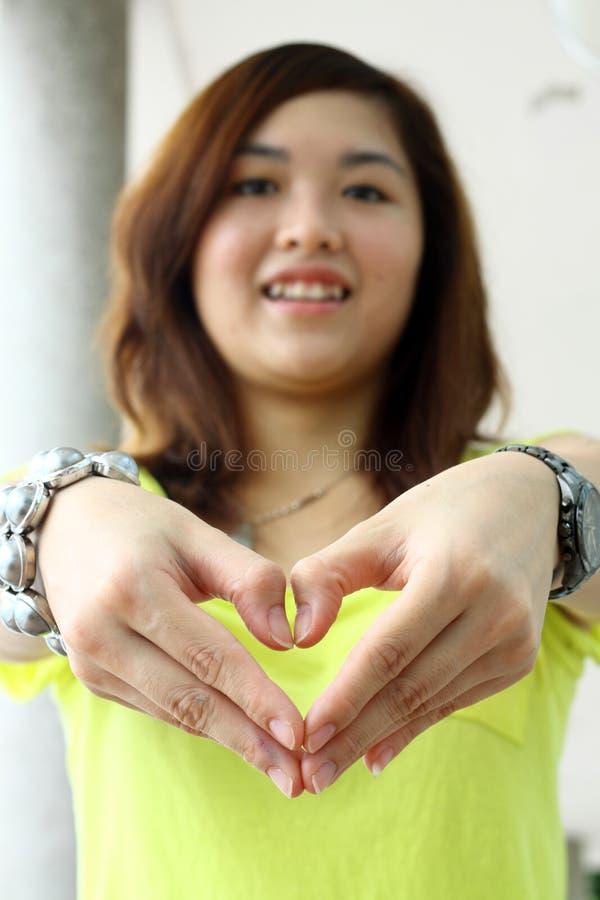 Una ragazza cinese fa un cuore immagine stock