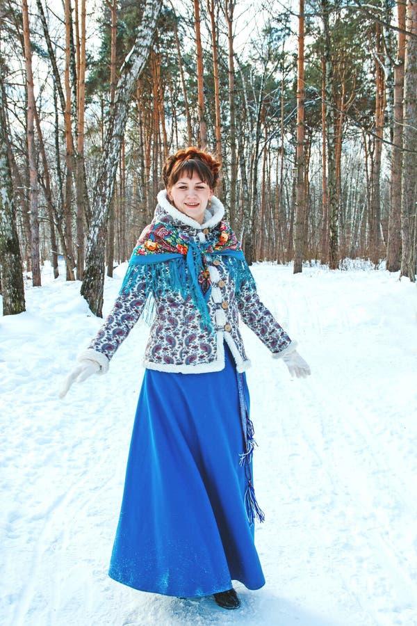 Una ragazza con bei capelli sulla sua testa in uno stile dello slavo nella piena crescita nella foresta di inverno fotografia stock libera da diritti