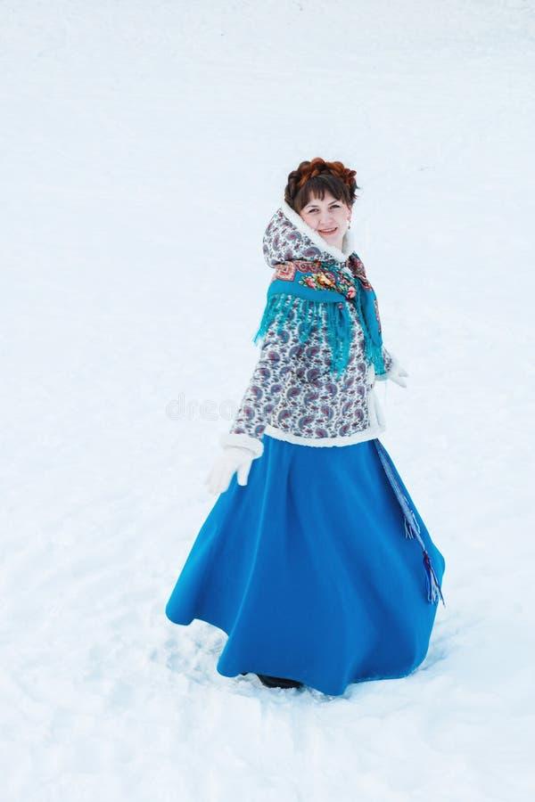 Una ragazza con bei capelli sulla sua testa in uno stile dello slavo nella piena crescita nella foresta di inverno immagini stock libere da diritti
