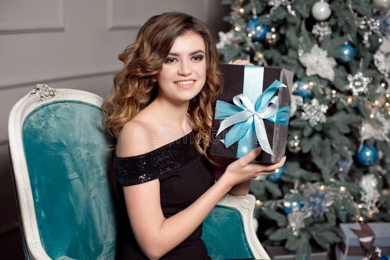 Una ragazza con capelli ondulati splendidi, trucco luminoso, tiene in sue mani un regalo avvolto, si siede di una in una sedia co immagine stock