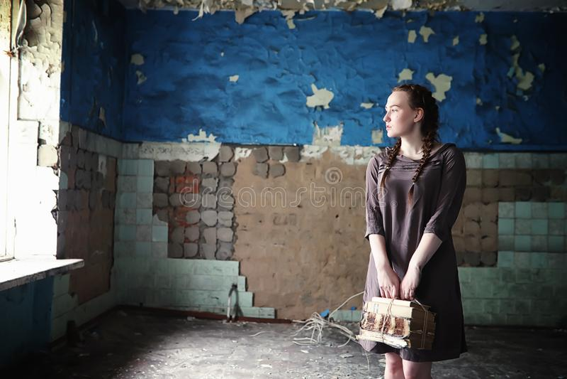Una ragazza con i vecchi libri nella vecchia casa immagini stock