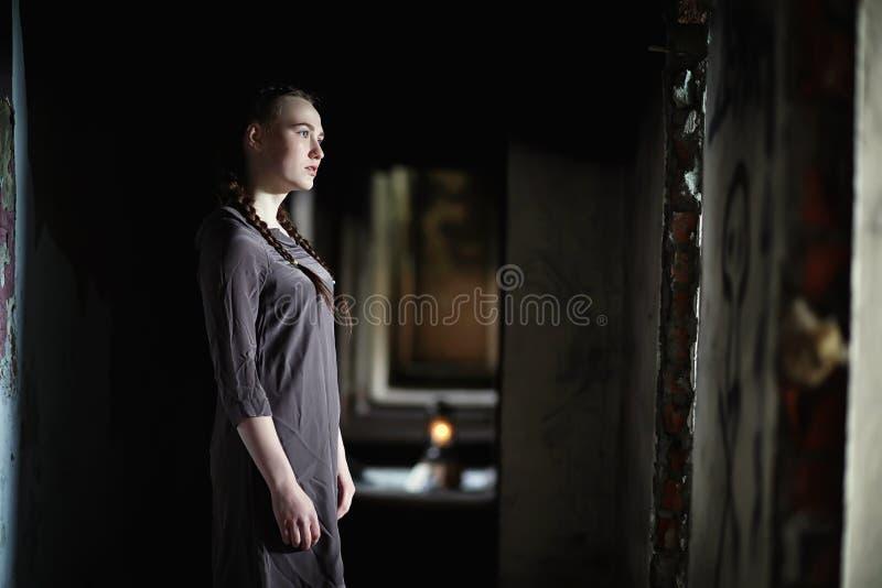 Una ragazza con i vecchi libri nella vecchia casa fotografia stock libera da diritti