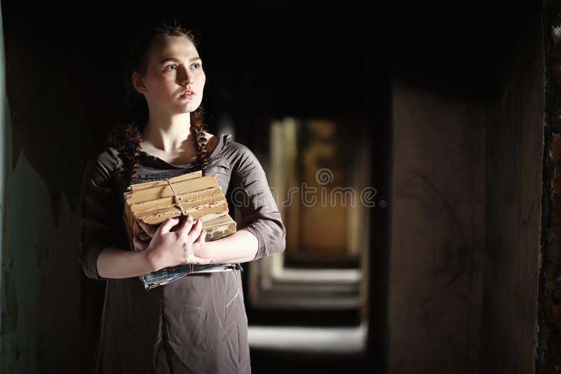 Una ragazza con i vecchi libri nella vecchia casa immagini stock libere da diritti