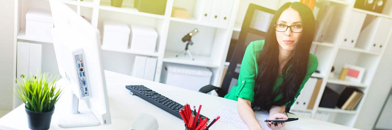 Una ragazza con i vetri nell'ufficio si siede alla tavola e tiene un telefono, una matita e un calcolatore in sue mani fotografie stock
