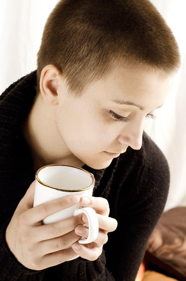 Una ragazza con il tè bevente di breve taglio di capelli fotografia stock