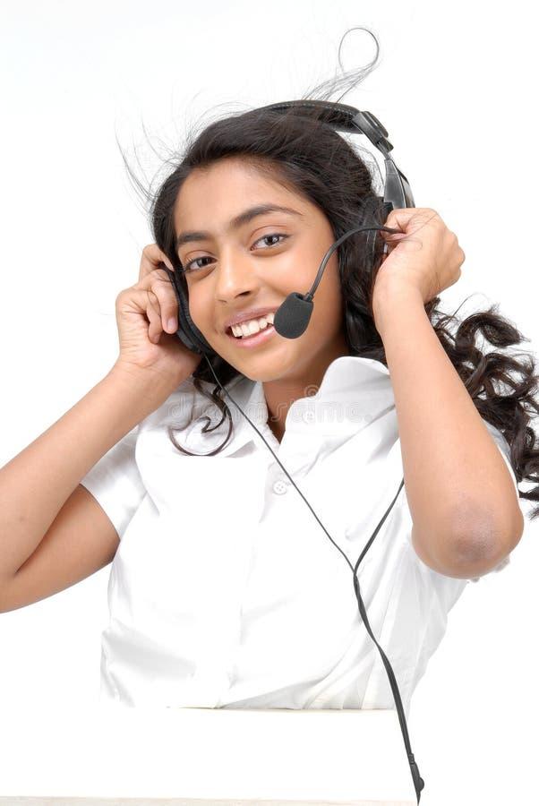 Una ragazza con le cuffie che ascolta la musica immagini stock