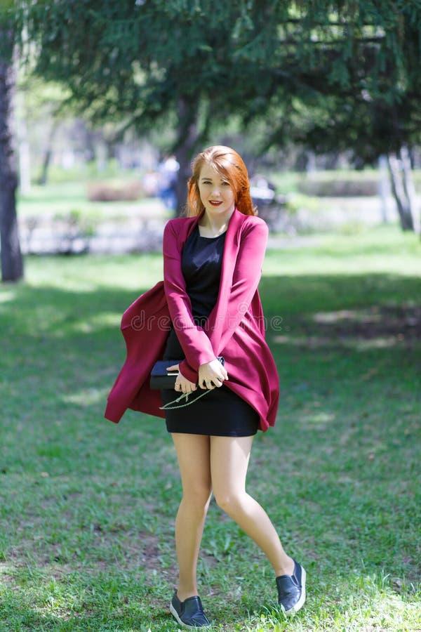 Una ragazza con le passeggiate rosse dei capelli nel parco di buon umore Ragazza felice fotografie stock