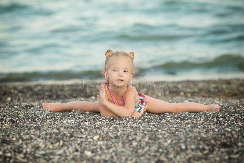 Una ragazza con sindrome di Down che si siede sulle spaccature fotografia stock libera da diritti