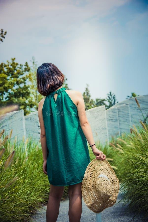 Una ragazza con un cappello di paglia in sua mano fotografia stock