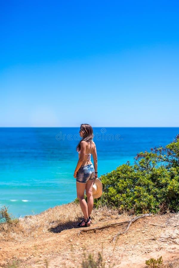 Una ragazza con un cappello in sue mani sta stando con la sua parte posteriore su una roccia contro l'oceano blu fotografie stock