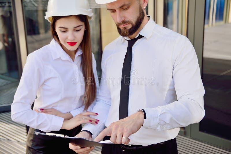 Una ragazza con un uomo in caschi bianchi della costruzione e camice bianche immagini stock libere da diritti
