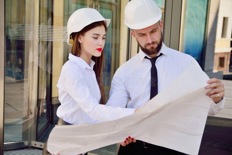 Una ragazza con un uomo in caschi bianchi della costruzione e camice bianche immagini stock