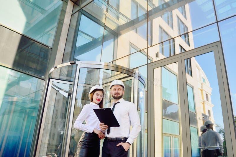 Una ragazza con un uomo in caschi bianchi della costruzione e camice bianche fotografia stock libera da diritti