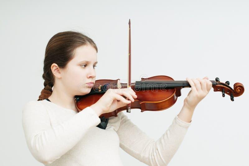 Una ragazza concentrata che gioca violino sopra fondo bianco fotografie stock libere da diritti