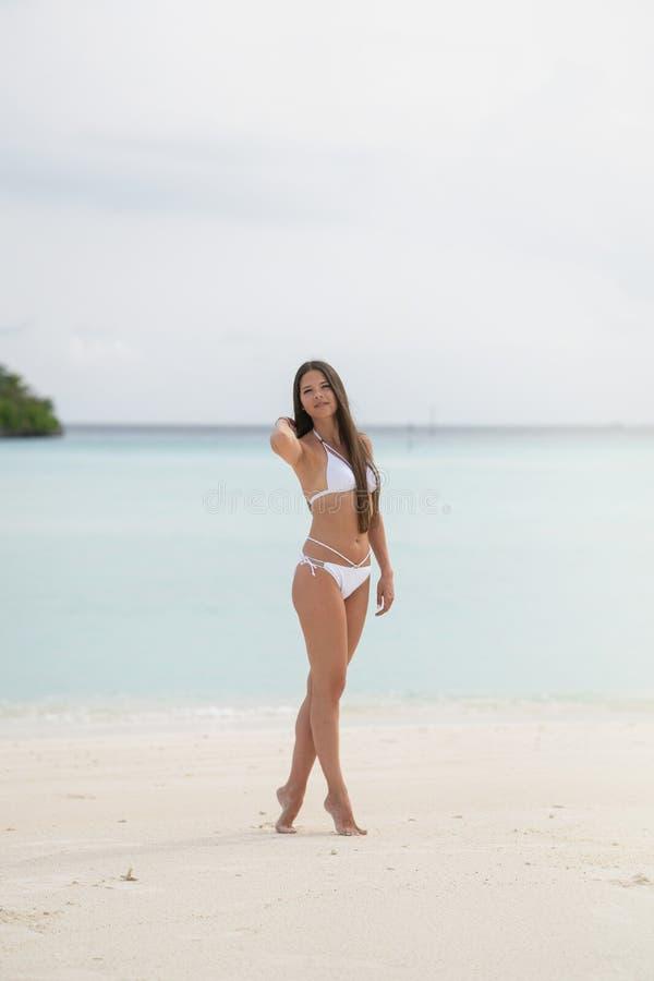 Una ragazza in una condizione bianca del costume da bagno sulla spiaggia Nei precedenti è l'acqua del turchese fotografia stock libera da diritti