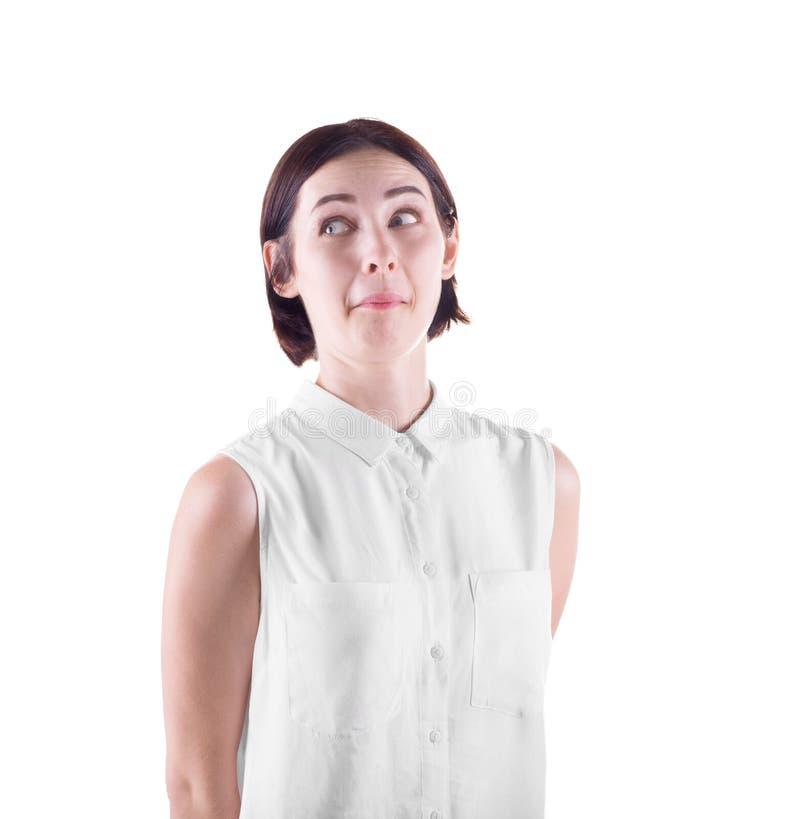 Una ragazza curiosa e divertente Una ragazza allegra in una camicia casuale Una signora maldestra isolata su un fondo bianco Uno  fotografie stock libere da diritti