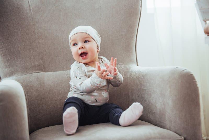 una ragazza da 1 anno che indossa i vestiti alla moda, sedentesi in una sedia d'annata nella stanza fotografia stock