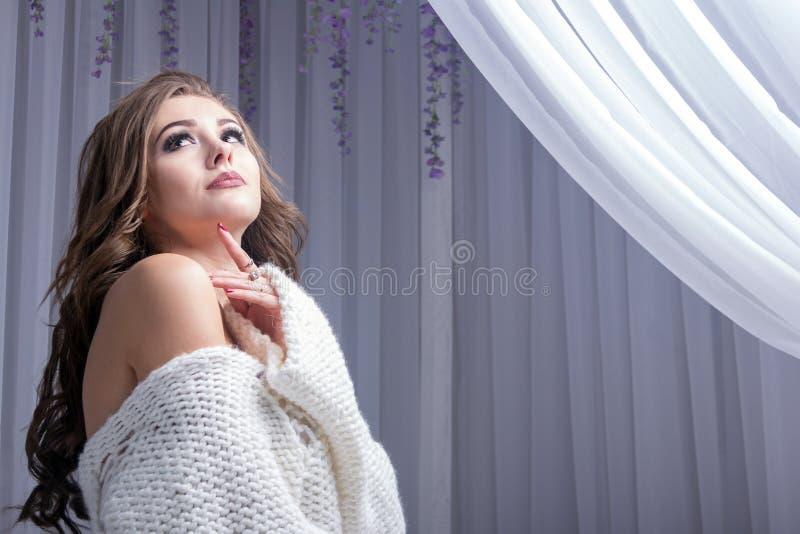 Una ragazza dai capelli lunghi molto bella con i cigli lunghi ed il manicure rosso in un maglione tricottato bianco guarda medita immagine stock