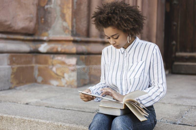 Una ragazza dalla carnagione scura si siede sui punti e tiene una compressa e la esamina Sui suoi piedi sono i libri fotografie stock