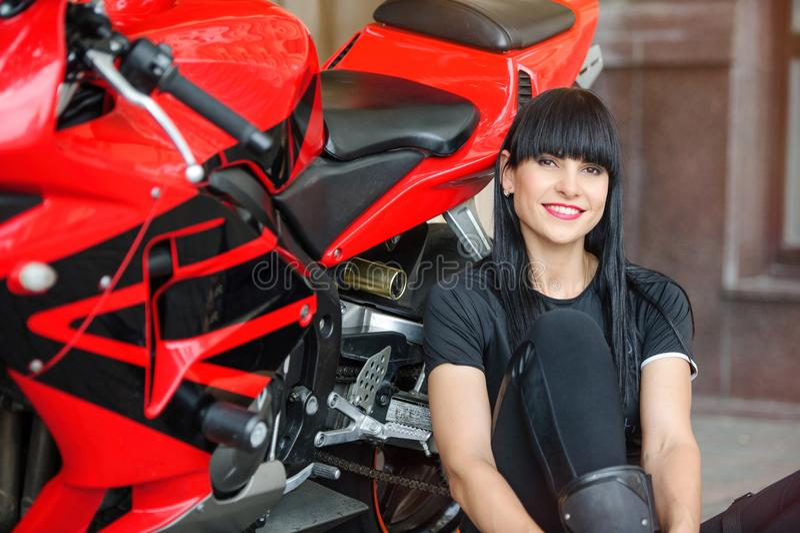 Una ragazza del motociclista in vestiti neri su un motociclo di sport che posa mentre sedendosi nella città immagini stock